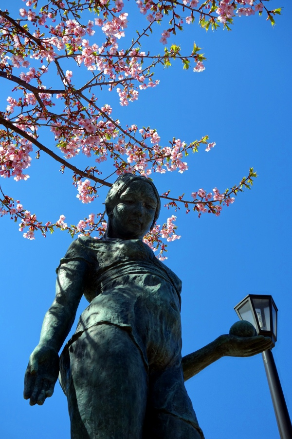 Statue of a woman below cherry blossoms at 千鳥ヶ淵 (Chidorigafuchi, Tokyo, Japan) on 15 March 2014.